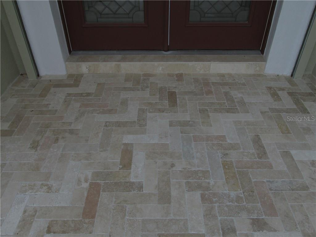 The front entrance landing is travertine laid in a beautiful herring bone pattern. - Single Family Home for sale at 3001 Rivershore Ln, Port Charlotte, FL 33953 - MLS Number is D5917929