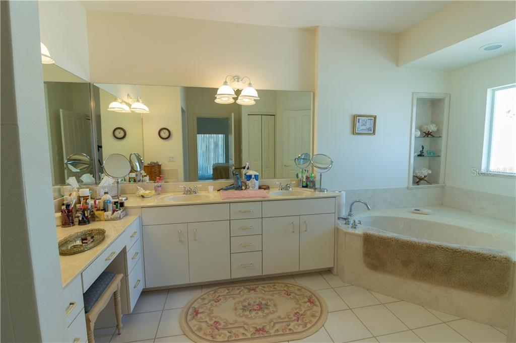 The master bath has a garden tub, dual sinks, a Roman shower and water closet.  His and her walk-in closets sit on either side of the entrance to the bath. - Single Family Home for sale at 1439 Deer Creek Dr, Englewood, FL 34223 - MLS Number is D5921060
