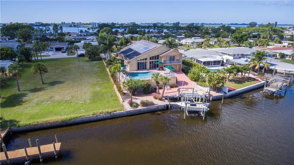 In this view you can see the solar panels on the south side of the roof, the sea walled waterfront and the boat lifts. - Single Family Home for sale at 1439 Deer Creek Dr, Englewood, FL 34223 - MLS Number is D5921060