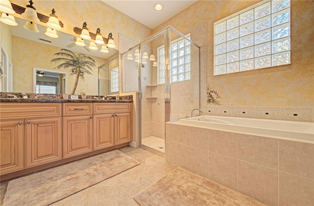 Master bathroom with double vanities, shower stall and Jacuzzi whirlpool tub - Single Family Home for sale at 409 Montelluna Drive, North Venice, FL 34275 - MLS Number is D5923522