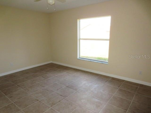 Rear Guest bedroom has tiled flooring, ceiling fan and walk in closet. - Single Family Home for sale at 7385 Teaberry St, Englewood, FL 34224 - MLS Number is D6101274