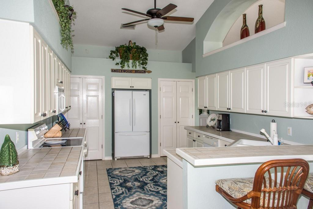 Another view of the kitchen.  Pantry on each side of the refrigerator. - Single Family Home for sale at 14 Long Meadow Ln, Rotonda West, FL 33947 - MLS Number is D6102683