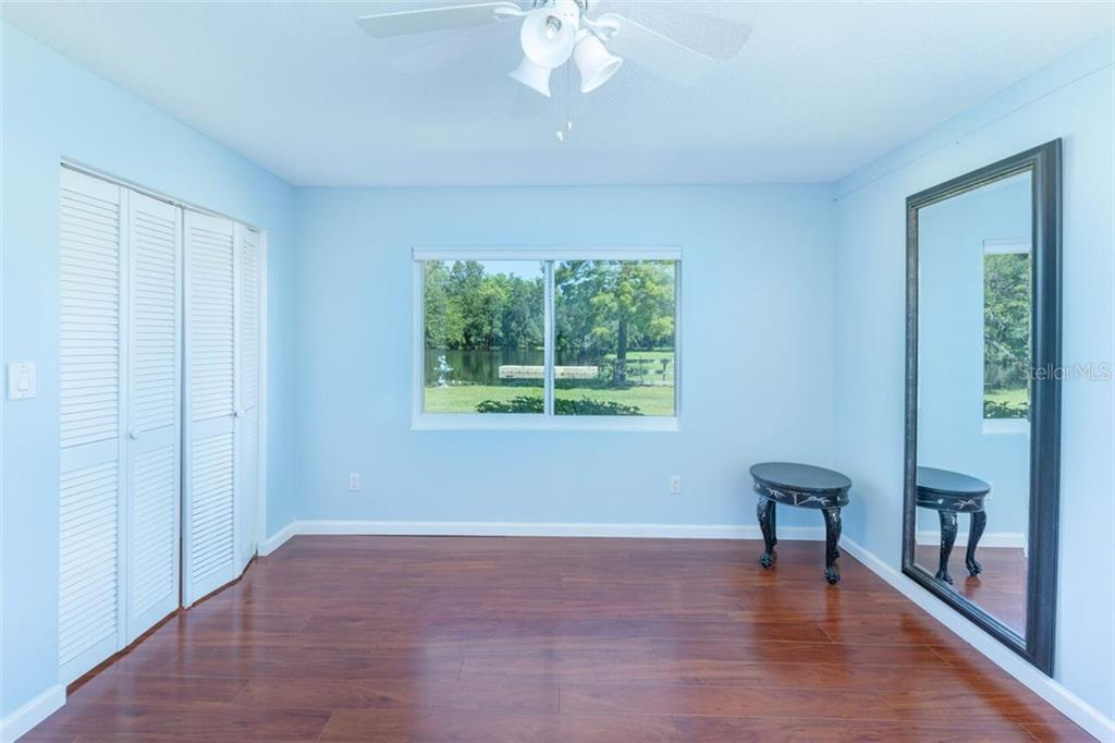 The second bedroom features 2 double closets with interior lighting, a pond view and variable speed ceiling fan - Single Family Home for sale at 7339 Hawkins Rd, Sarasota, FL 34241 - MLS Number is D6102762