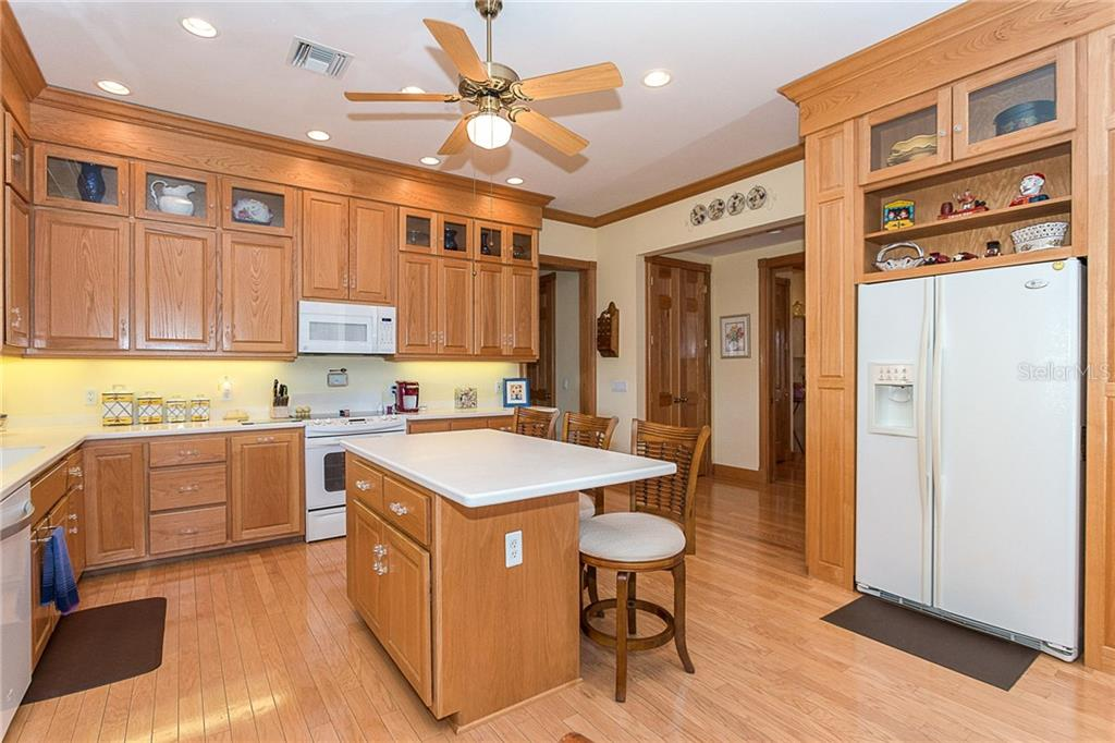 This large kitchen is the hub of the home with warm wood floors, recessed lighting and beautiful custom wood cabinetry. - Single Family Home for sale at 550 S Oxford Dr, Englewood, FL 34223 - MLS Number is D6111512
