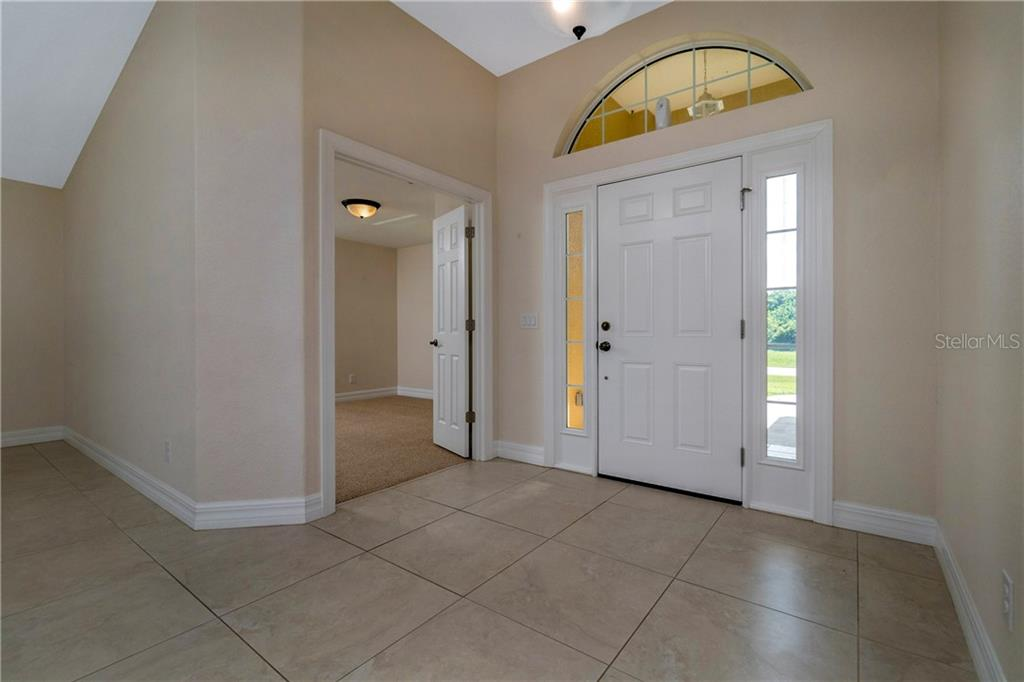 JUST INSIDE THE FRONT DOOR LOOKING AT THE ENTRY FOYER AND THE OPEN DOOR TO BEDROOM # 3. - Single Family Home for sale at 112 Boxwood Ln, Rotonda West, FL 33947 - MLS Number is D6114179