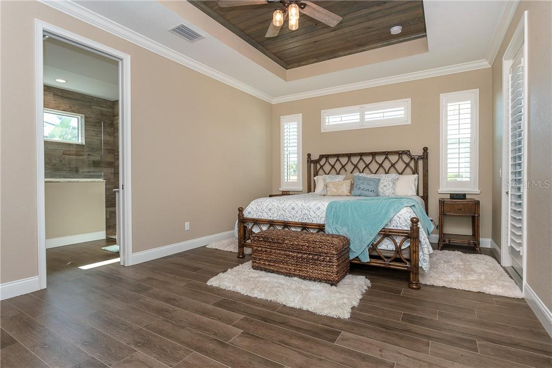 Bedroom 1 - master suite with cypress inlaid ceiling, private access to the lanai, ensuite and large walk-in closet - Single Family Home for sale at 145 Leland St Se, Port Charlotte, FL 33952 - MLS Number is D6117438