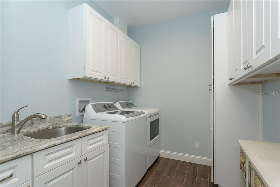Laundry room has the same beautiful granite as the rest of the house and lots of storage space - Single Family Home for sale at 145 Leland St Se, Port Charlotte, FL 33952 - MLS Number is D6117438