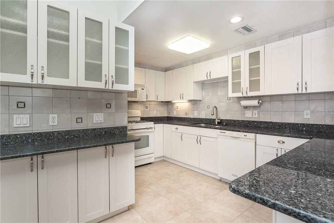 Beautiful Granite Counters with upgraded Shaker Cabinets and see through cabinets for your specialty dishes - Single Family Home for sale at 1661 New Point Comfort Rd, Englewood, FL 34223 - MLS Number is D6117712