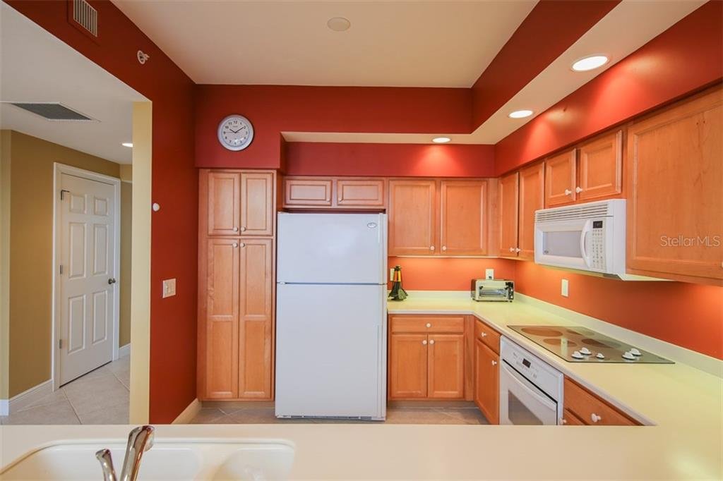 Honey color wood cabinetry, solid surface counters, pantry plus great task lighting makes this cheerful kitchen a delight to work in! - Condo for sale at 3313 Sunset Key Cir #402, Punta Gorda, FL 33955 - MLS Number is C7236886