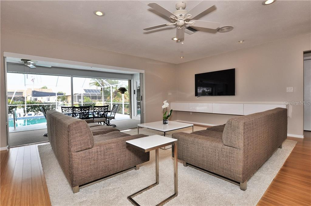 Open living room floor plan with pocket doors to the lanai and pool area - Single Family Home for sale at 2526 Parisian Ct, Punta Gorda, FL 33950 - MLS Number is C7249726