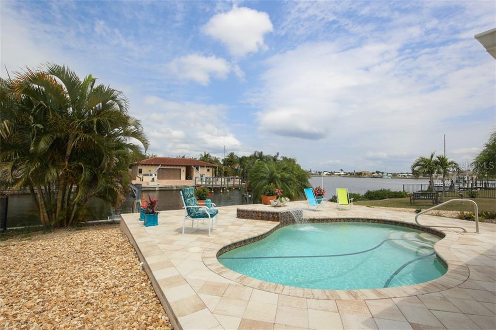 Gorgeous heated saltwater pool with waterfall overlooks Edgewater Lake - Single Family Home for sale at 158 Morgan Ln Se, Port Charlotte, FL 33952 - MLS Number is C7400633