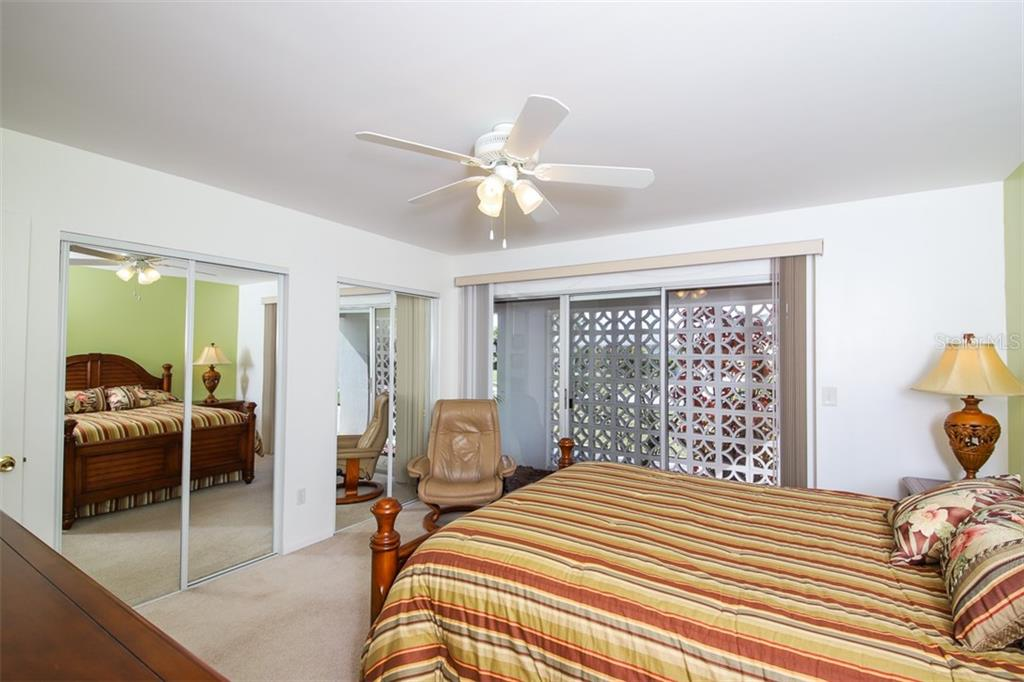 Owner Suite with sliders to front porch & dual closets with mirrored by-pass doors. - Single Family Home for sale at 126 Bangsberg Rd Se, Port Charlotte, FL 33952 - MLS Number is C7409866