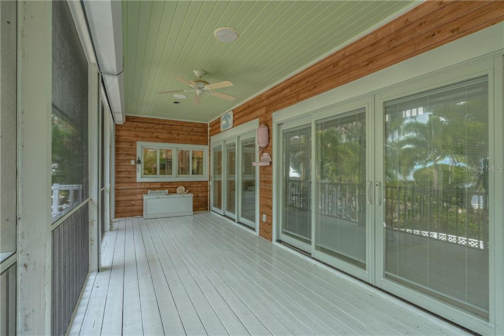 Back porch with impact glass sliding doors, kitchen pass through. The perfect place for a lazy afternoon - Single Family Home for sale at 124 Useppa Is, Captiva, FL 33924 - MLS Number is C7419408
