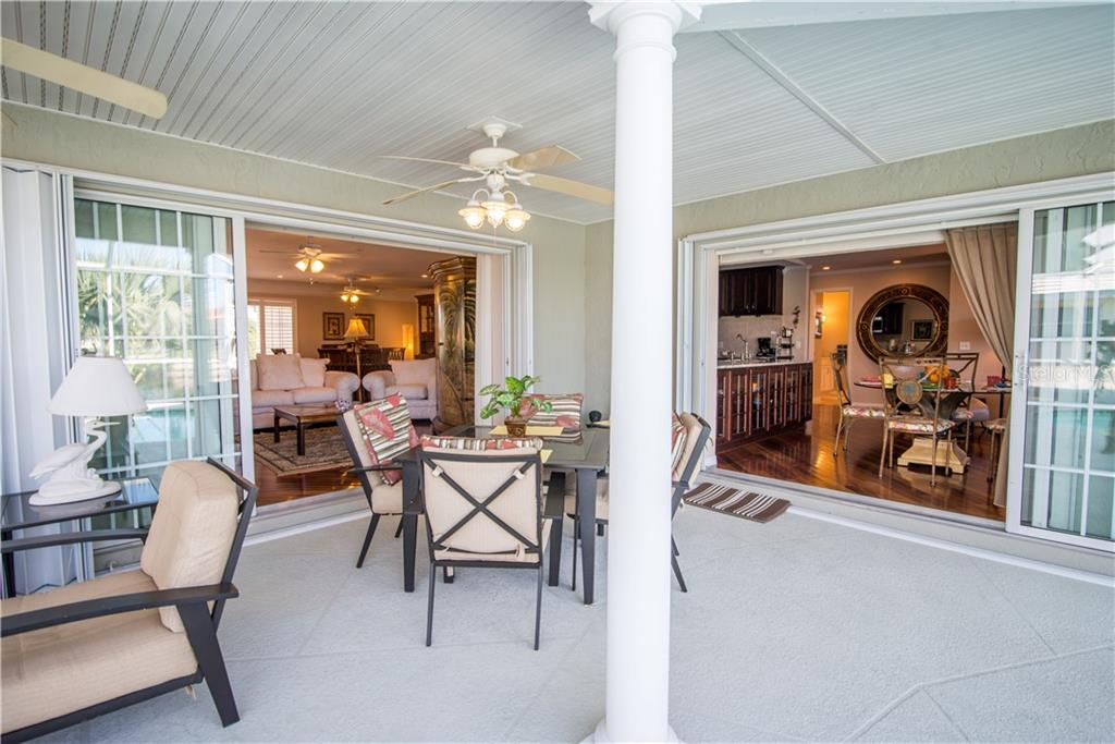 View from the covered lanai to the living room on the left and great room/kitchen on the right. Newer sliders add a touch of class. - Single Family Home for sale at 1440 Appian Dr, Punta Gorda, FL 33950 - MLS Number is C7425399