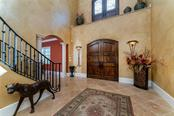 Enter through grand French doors to find a massive foyer, towering ceiling, a flowing floorplan, tile flooring, and warm hues. - Single Family Home for sale at 7440 Riverside Dr, Punta Gorda, FL 33982 - MLS Number is C7436263