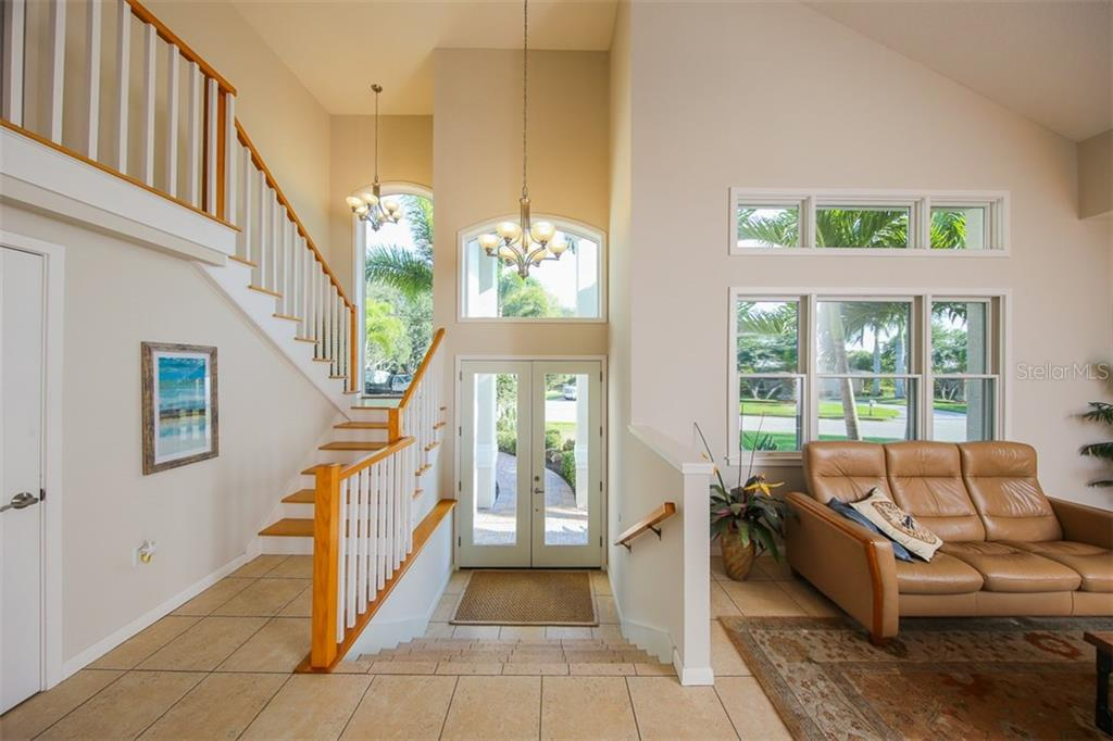 Foyer, Living room and staircase to second level - Single Family Home for sale at 827 Paradise Way, Sarasota, FL 34242 - MLS Number is A4167744