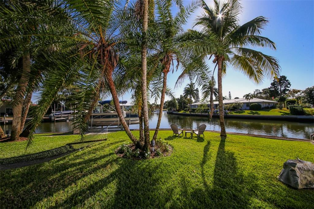 Professional landscaping with expansive backyard, full water views with access to the boat lift and dock. - Single Family Home for sale at 5281 Cape Leyte Way, Sarasota, FL 34242 - MLS Number is A4171478