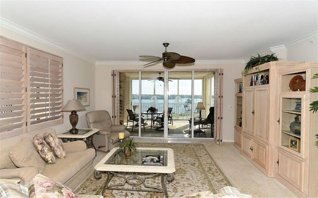 Living room with sliders to enclosed balcony with bay views - Condo for sale at 1260 Dolphin Bay Way #401, Sarasota, FL 34242 - MLS Number is A4173008