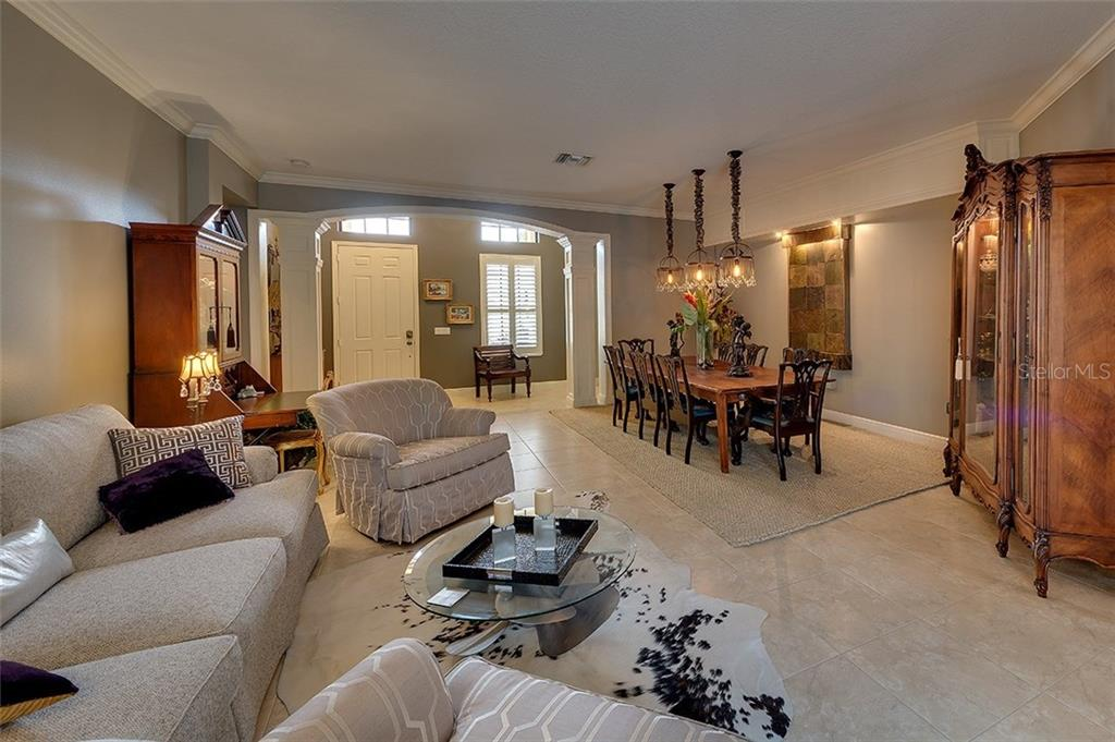 Beautiful entry with archway and columns leads into a large living room  with formal dining area - Single Family Home for sale at 7254 Lake Forest Gln, Lakewood Ranch, FL 34202 - MLS Number is A4174107