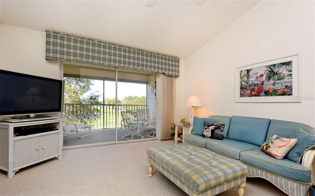 Vaulted ceilings enhance the open feel of this bright condo.  Sliders to the screened patio. - Condo for sale at 8750 Olde Hickory Ave #9305, Sarasota, FL 34238 - MLS Number is A4178271
