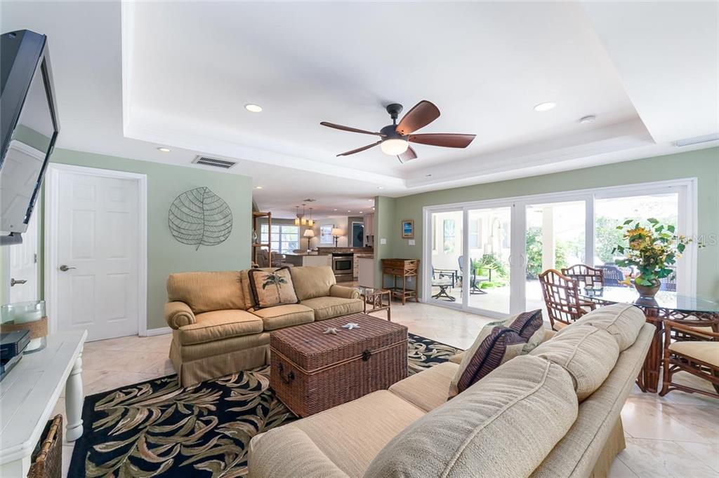 Wall of glass extends the great room to a covered dining area with synchronized ceiling fans. - Single Family Home for sale at 413 Bay Palms Dr, Holmes Beach, FL 34217 - MLS Number is A4184679
