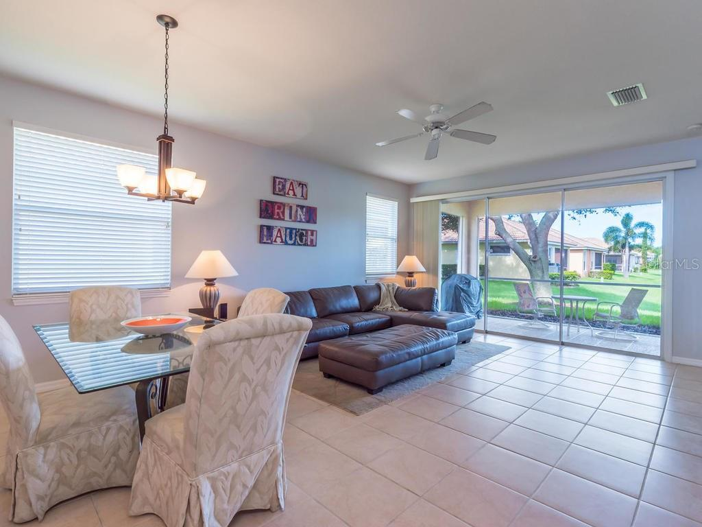 Living/Dining room with sliders to lanai - Single Family Home for sale at 4294 Reflections Pkwy, Sarasota, FL 34233 - MLS Number is A4185695