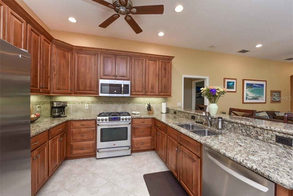 Chef's kitchen with natural gas cooktop and electric oven. Note granite counters and lovely wood cabinetry. - Single Family Home for sale at 4851 Sweetshade Dr, Sarasota, FL 34241 - MLS Number is A4186306