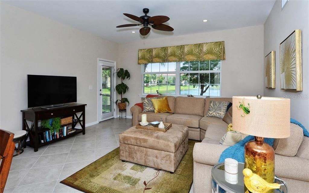 Living room with lake views - Condo for sale at 81 Navigation Cir #103, Osprey, FL 34229 - MLS Number is A4188370