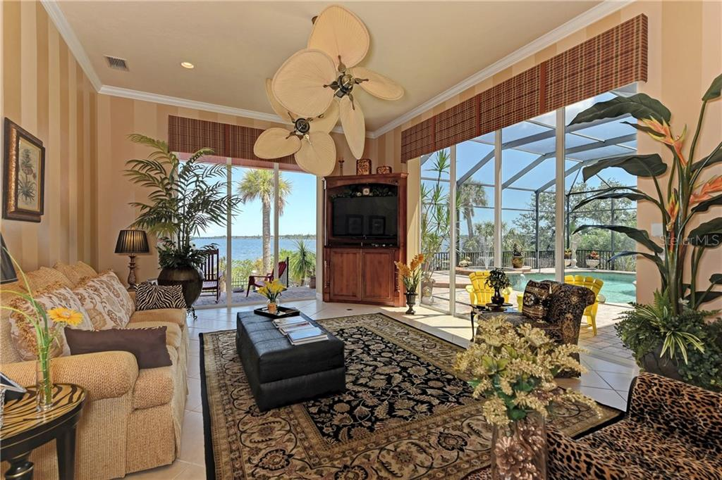 Family Room opens to pool with cascading doors, or to covered patio overlooking the river. Walls are faux paint. - Single Family Home for sale at 370 Highland Shores Dr, Ellenton, FL 34222 - MLS Number is A4188456