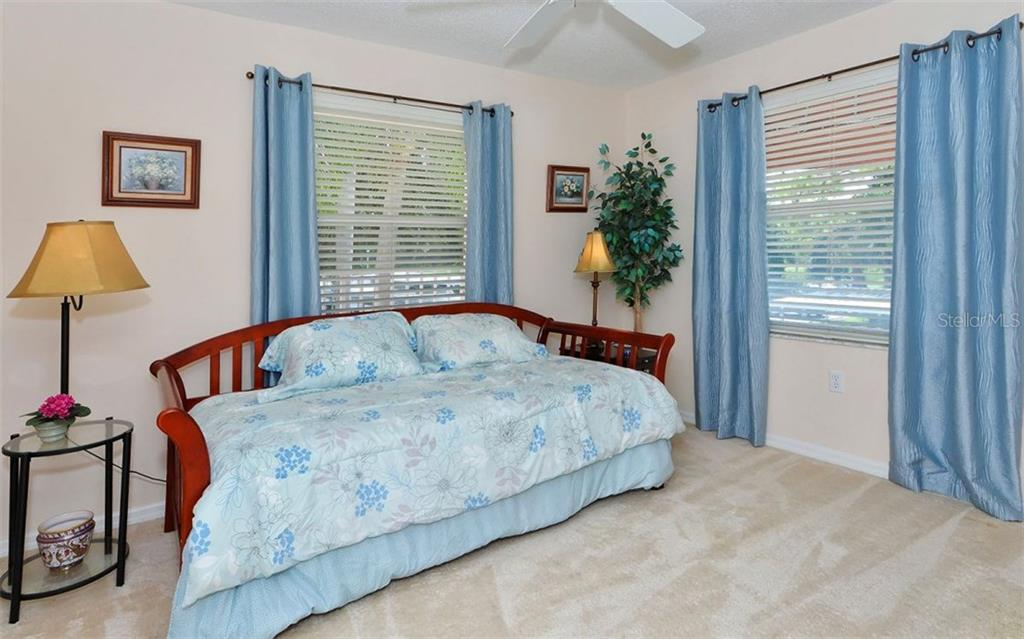 Guest bedroom with multiple windows.  End unit privacy abounds. Bed is a trundle. - Condo for sale at 9300 Clubside Cir #1201, Sarasota, FL 34238 - MLS Number is A4192821