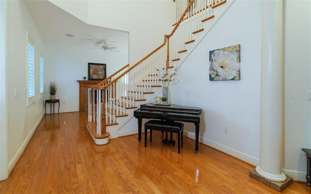 Inviting foyer with music room or sitting room to the left and beautiful staircase leading to four bedrooms and 3 baths upstairs - Single Family Home for sale at 9818 9th Ave Nw, Bradenton, FL 34209 - MLS Number is A4194125