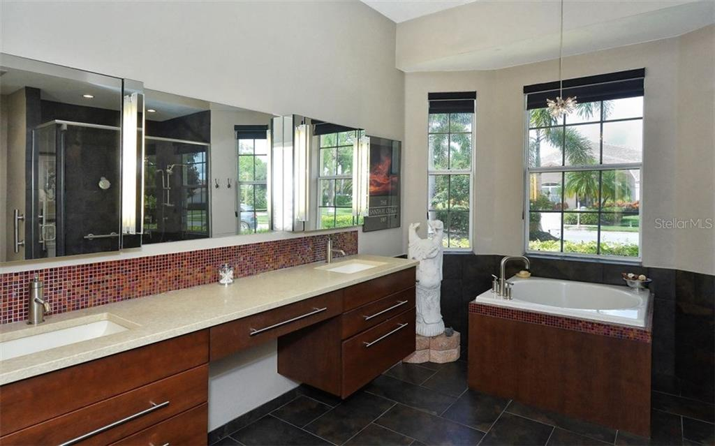 Master bath boasts double sinks, solid surface counters, lighted mirrors, tiled floors and a Japanese soaking tub. - Single Family Home for sale at 8747 Grey Oaks Ave, Sarasota, FL 34238 - MLS Number is A4195019