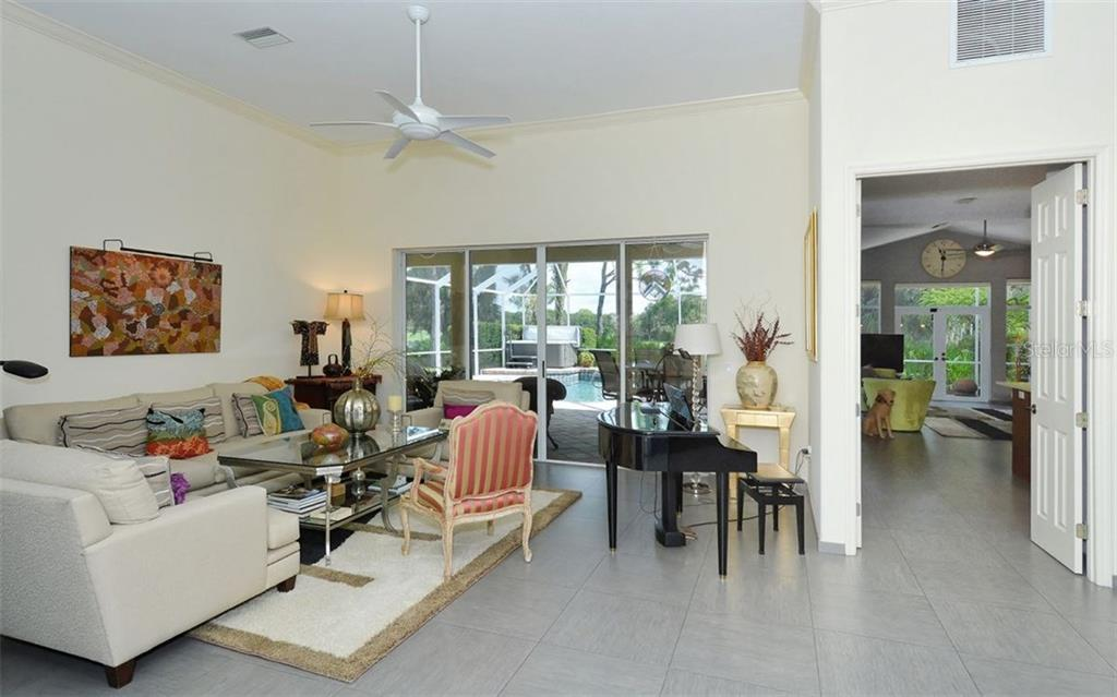 This picture is taken from the front entrance. Open floor plan allows full view of lanai and family room. Living room has triple sliders to the lanai. - Single Family Home for sale at 8747 Grey Oaks Ave, Sarasota, FL 34238 - MLS Number is A4195019