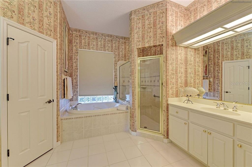 Master bathroom with double sinks, shower, tub and remote control blind on window above the tub! - Single Family Home for sale at 618 Sawgrass Bridge Rd, Venice, FL 34292 - MLS Number is A4195740