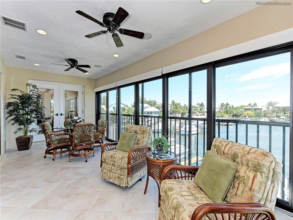Climate controlled enclosed balcony with a birds-eye view of the marina. - Condo for sale at 4106 Marina Ct #622, Cortez, FL 34215 - MLS Number is A4195845