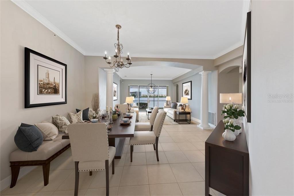 Virtually staged dining and living room with view to the lake. - Condo for sale at 6415 Moorings Point Cir #102, Lakewood Ranch, FL 34202 - MLS Number is A4196054