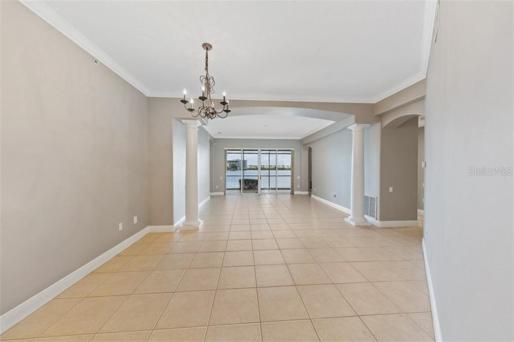 Large and open living and dining room with view to the lake beyond. - Condo for sale at 6415 Moorings Point Cir #102, Lakewood Ranch, FL 34202 - MLS Number is A4196054