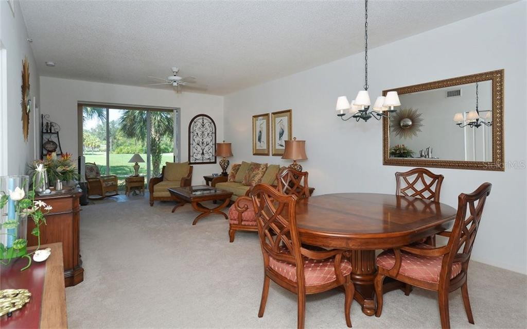 Living room/dining room combo. Slider to glass enclosed tiled lanai.  Excellent golf course views. - Condo for sale at 9570 High Gate Dr #1712, Sarasota, FL 34238 - MLS Number is A4196327