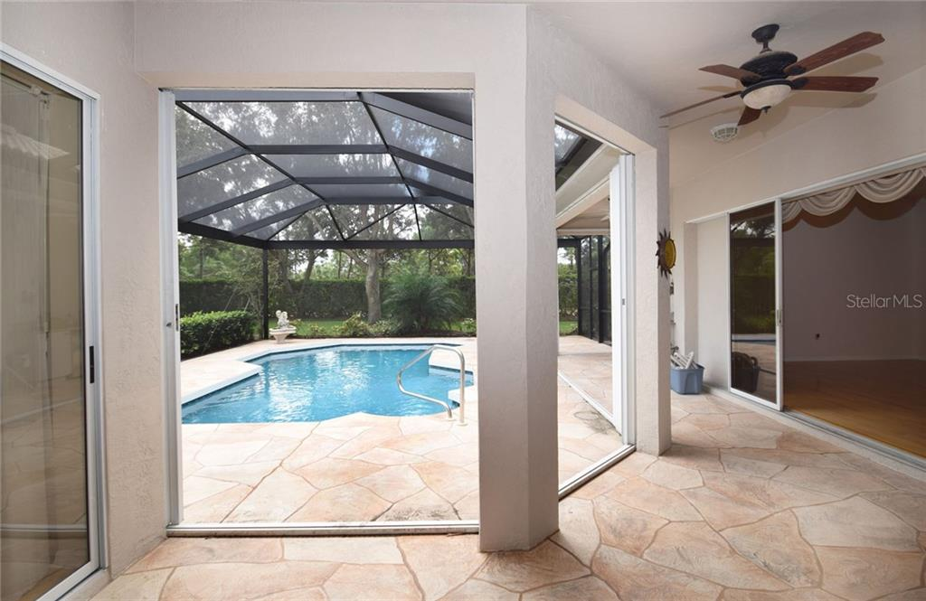 Covered lanai pool area with permanently installed retractable hurricane doors. - Single Family Home for sale at 9520 Hawksmoor Ln, Sarasota, FL 34238 - MLS Number is A4197662