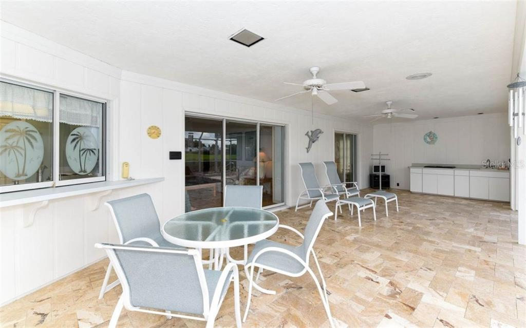 Travertine Lanai Features Large Sitting Area, Enough to Accommodate 2 Sitting Areas, Pass Through Window, Kitchen with Wet bar and separate pool bath and storage closet - Single Family Home for sale at 1632 Valley Dr, Venice, FL 34292 - MLS Number is A4197771