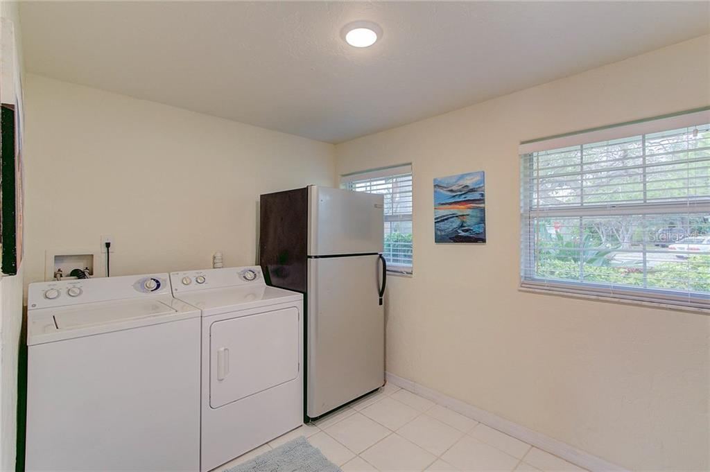 With space for an additional refrigerator, the laundry room has built-in shelving and is also currently used as a walk-in pantry. - Single Family Home for sale at 501 70th St, Holmes Beach, FL 34217 - MLS Number is A4205799
