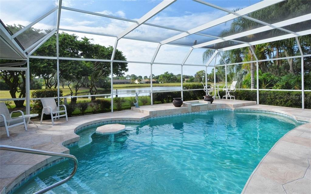 Looking out to lake and golf course.  Heated salt water pool with table - Single Family Home for sale at 3882 Spyglass Hill Rd, Sarasota, FL 34238 - MLS Number is A4206477