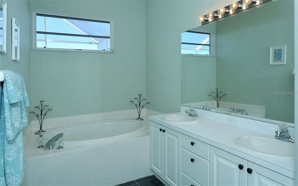 Master bath with garden/soaking tub and double sinks. - Villa for sale at 9554 Forest Hills Cir, Sarasota, FL 34238 - MLS Number is A4206506