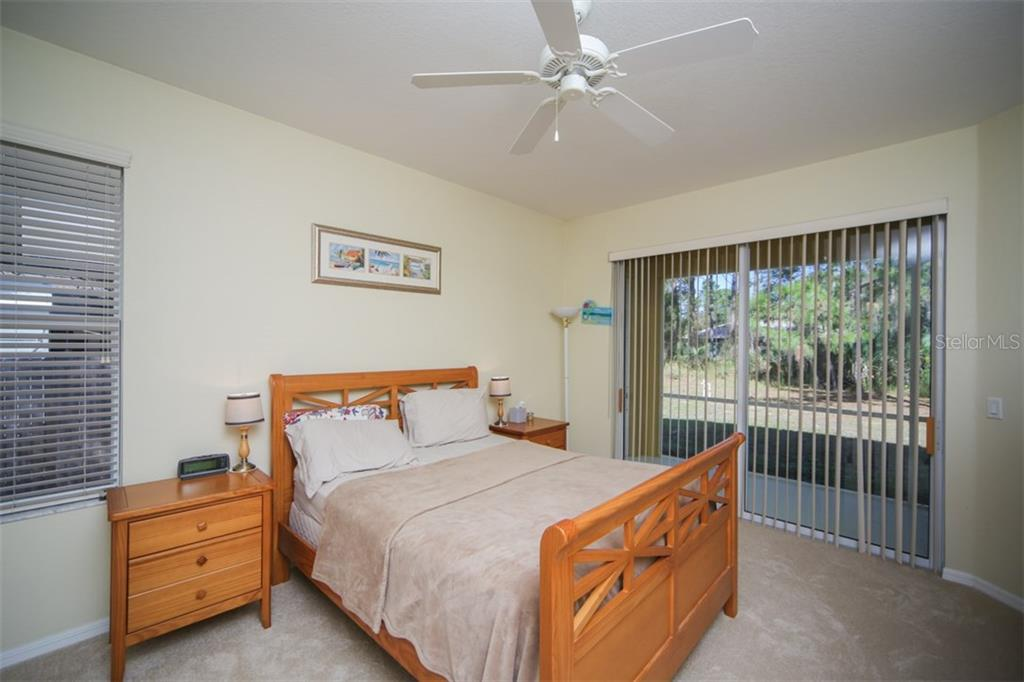 Master bedroom with sliders to lanai - Single Family Home for sale at 1876 Bushnell Ave, North Port, FL 34286 - MLS Number is A4207073