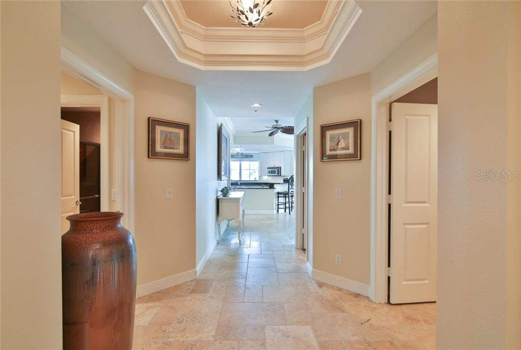 Front entry hall-tray ceiling, travertine floors throughout - Condo for sale at 1310 Old Stickney Point Rd #e21, Sarasota, FL 34242 - MLS Number is A4209502