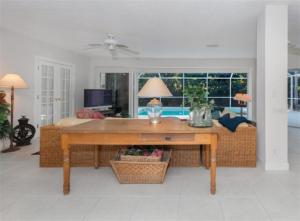 Living room with sliders to pool - Single Family Home for sale at 445 Mahon Dr, Venice, FL 34285 - MLS Number is A4209507