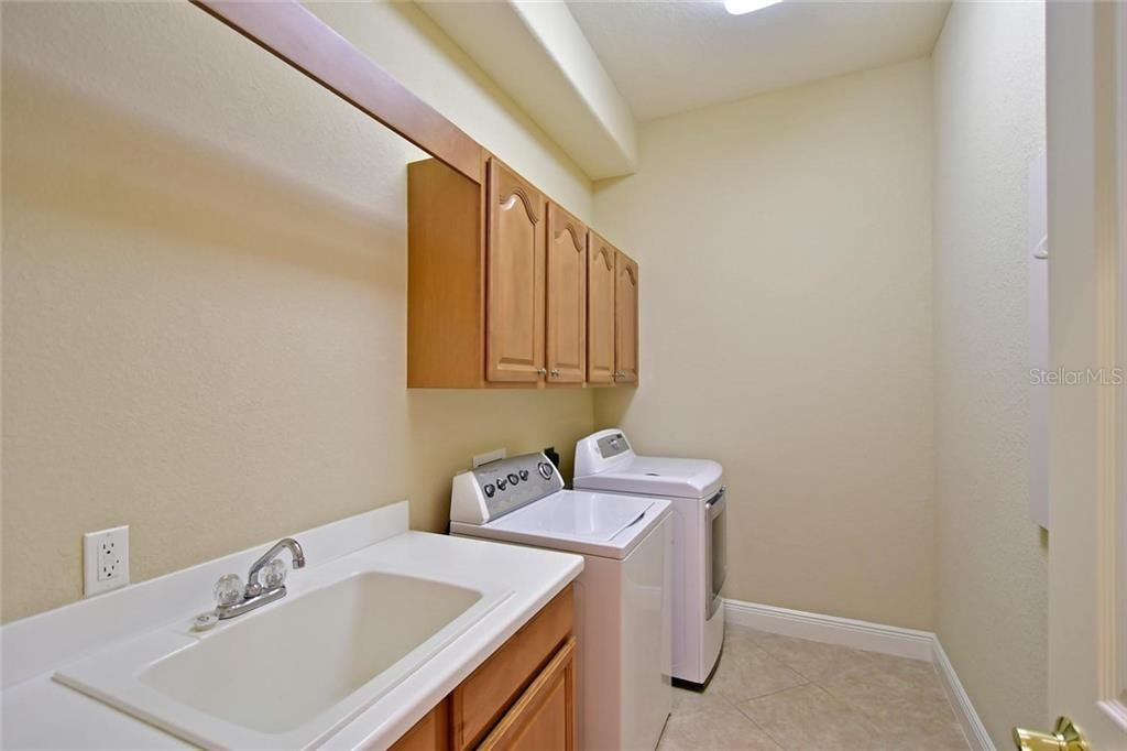 Large laundry room with wooden cabinets and the convenience of a bar above the sink for hanging clothes that need to be air dried. - Single Family Home for sale at 3729 Summerwind Cir, Bradenton, FL 34209 - MLS Number is A4215992