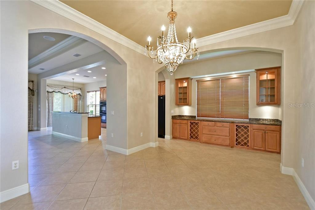 Tray ceilings in dining room and great room with extensive crown moulding.  Chandeliers convey.  Buyer will enjoy the glass front cabinets and wine racks in this  exquisite Butler pantry. - Single Family Home for sale at 3729 Summerwind Cir, Bradenton, FL 34209 - MLS Number is A4215992