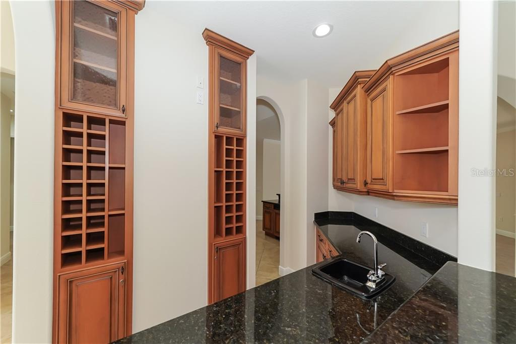 Butler's Pantry/Entertainment Bar. Granite countertops, custom cabinets with built-in wine racks and wine refrigerator. - Single Family Home for sale at 13219 Palmers Creek Ter, Lakewood Ranch, FL 34202 - MLS Number is A4407857