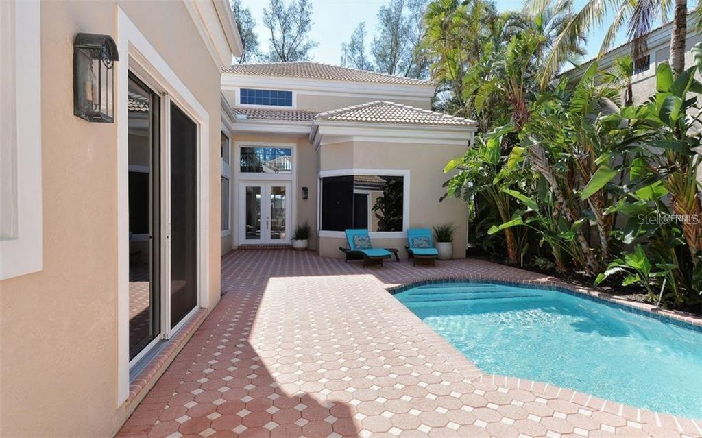 The view of the pool from the front entrance; pavers were installed in 2017 - Single Family Home for sale at 3529 Fair Oaks Ln, Longboat Key, FL 34228 - MLS Number is A4414992
